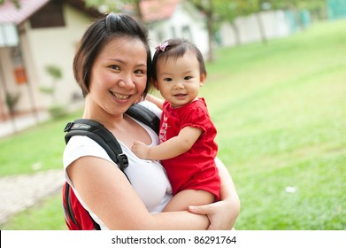 Eleven month old Asian baby girl and her mother in a park