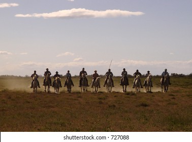 eleven silhouetted cowboys in straight line riding in dusty field