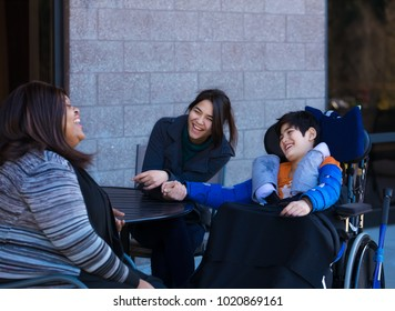 Eleven year old disabled biracial Asian Caucasian boy in wheelchair outdoors, sitting and talking with his two multiethnic caregivers