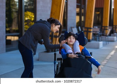 Eleven year old disabled boy in wheelchair listening to music with earbuds with the help of caregiver. Has cerebral palsy.