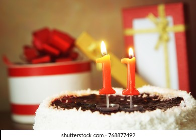 Eleven years birthday. Cake with burning candles and gifts