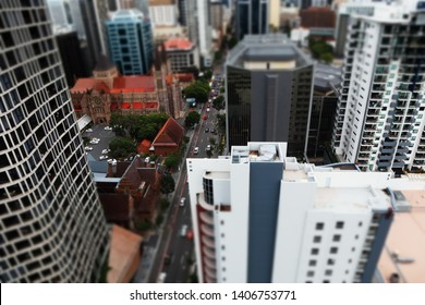 Elevted view of city with church and buildings in minature effect. Main roda with cars lined by trees. Tall buildings office and residental apartments surround the church and road.