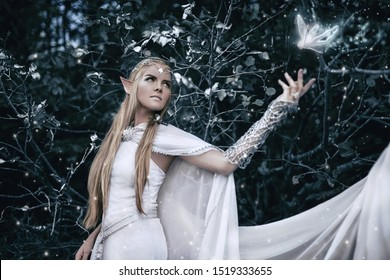 Elf with long white hair in the forest. magical photo shoot. fairy tale. beautiful girl in a white dress. fancy silver accessories