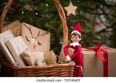 Elf on the shelf with basket of Christmas gifts near Christmas tree. Christmas presents wrapped in craft paper and nice elf toy.