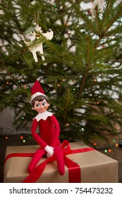 Elf on the shelf sitting on Christmas gifts near Christmas tree. Christmas presents wrapped in craft paper and nice elf toy.