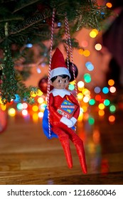 Elf on the shelf sitting on a swing with a gift. Elf on the shelf sitting on the Chrisrmas tree. Beautiful bokeh from the Christmas lights. Beautiful background