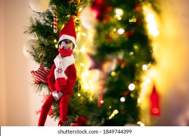 Elf on the shelf wearing face mask. Christmas decoration in coronavirus pandemic. Seasonal home design in covid-19 outbreak. Xmas tree and fireplace wreath.