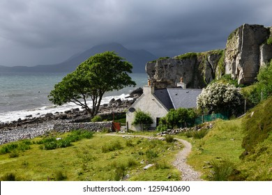 Elgol, Isle of Skye, Scotland, UK - June 14, 2018: House under cliff at Elgol beach with Red Cuillin Mountains under clouds at Loch Scavaig Scottish Highlands Isle of Skye Scotland UK