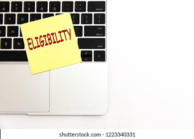 Eligibility writing text post it paper in office on laptop computer keyboard.  Concept of Less Eligibility. top view.