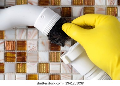Elimination of blockage in sewer pipes. Hands in yellow gloves disassemble and clean the sink siphon.