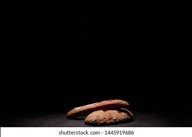 Eliptic form bread on a black background, bread from a stove on dark boards, a dough for a designer, copy space, rustic style, minimalism, top view, bakery