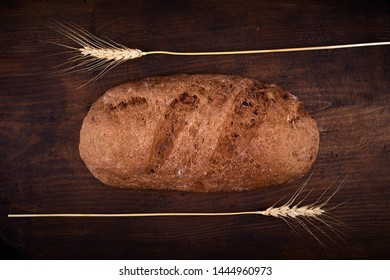 Eliptic form bread on a wooden background, bread from a stove on dark boards, a dough for a designer, copy space, rustic style, minimalism, top view, bakery