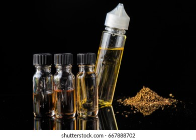 E-liquid bottles next to grinded tobacco leaves