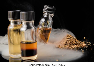 E-liquid bottles next to grinded tobacco leaves and smoke cloud