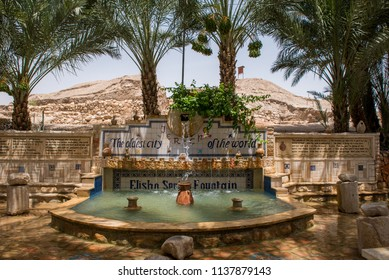 Elisha Spring Fountain at the entrance to the Jericho  site.  oldest city in the world at 10,000 years. In the shade of date palm trees with the hill of  the remains of Jericho in the sunny background