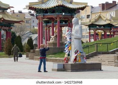 Elista, Russia: 04.19.2019. Buddhist complex Golden Abode of Buddha Shakyamuni in Kalmykia (Great Hurul). Woman praying in front of the statue of Tsagan Aav or the White Elder