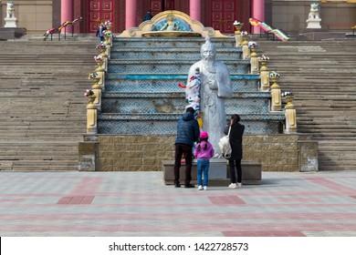 Elista, Russia: 04.19.2019. Buddhist complex Golden Abode of Buddha Shakyamuni in Kalmykia (Great Hurul). Family praying in front of the statue of Tsagan Aav or the White Elder