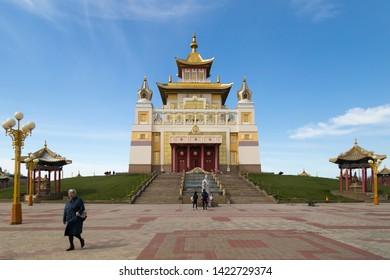 Elista, Russia: 04.19.2019. Buddhist complex Golden Abode of Buddha Shakyamuni in Kalmykia. Old woman walks across the square in front of the Great Hurul.