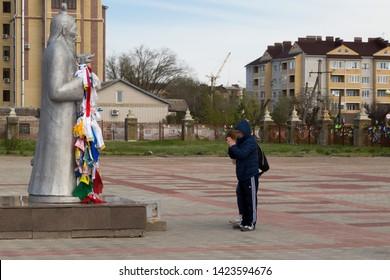 Elista, Russia: 04.19.2019. Buddhist complex Golden Abode of Buddha Shakyamuni in Kalmykia (Great Hurul). Man praying in front of the statue of Tsagan Aav or the White Elder
