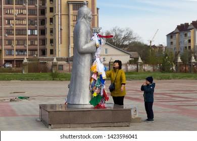 Elista, Russia: 04.19.2019. Buddhist complex Golden Abode of Buddha Shakyamuni in Kalmykia (Great Hurul). Woman and boy praying in front of the statue of Tsagan Aav or the White Elder