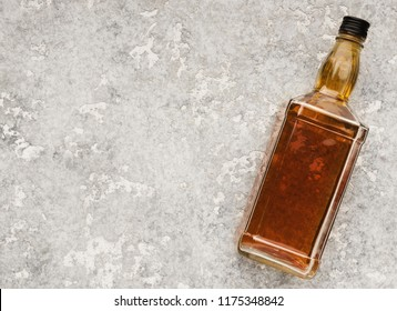 Elite alcohol bottle on gray stone background. Mockup for whiskey, brandy or cognac advertisement, top view, copy space