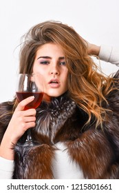 Elite leisure. Lady fashion model curly hairstyle enjoy elite wine. Wine culture concept. Woman drink wine. Reasons drink red wine in wintertime. Girl fashion makeup wear fur coat hold glass alcohol.