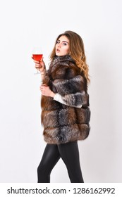 Elite leisure. Lady fashion model curly hairstyle enjoy elite wine. Wine culture concept. Reasons drink red wine in wintertime. Woman drink wine. Girl fashion makeup wear fur coat hold glass alcohol.