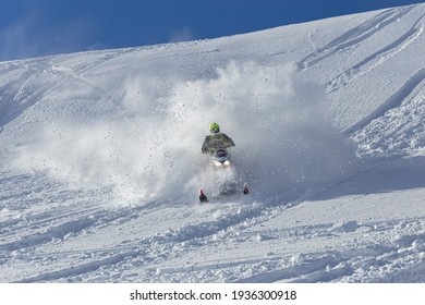elite sports snowmobiler rides and jumps on steep mountain slope with swirls of snow storm. background of blue sky leaving a trail of splashes of white snow. bright snowmobile and suit without brands
