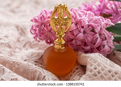 Elixir or Perfume Bottle on Pink background and flowers