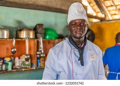 Eliye Springs, Lake Turkana, Kenya, Africa, June 15, 2018: Portrait of young male African chef standing in the restaurant kitchen. He is wearing a white double breasted jacket and toque.