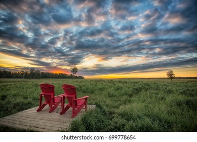Elk Island national park with red chairs before a dramatic sunrise.