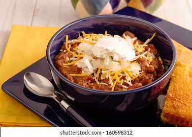 Elk meat chili with beans, sour cream, shredded cheese, diced onions in bowl sitting on blue plate with cornbread