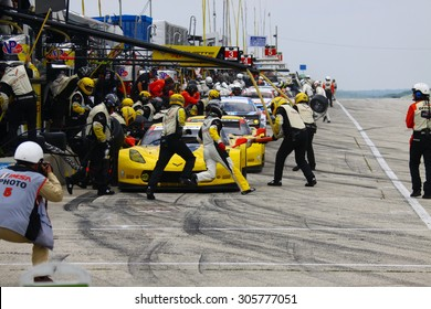 Elkhart Lake, Wisconsin USA - August 9, 2015: Road America road course, IMSA - Corvette racing team cars make tire, fuel pit stop. Drivers running to change. Corvette C7.R IMSA Tudor GT Le Mans class.
