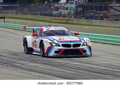 Elkhart Lake, Wisconsin USA - August 9, 2015: Road America road course, IMSA. BMW Team RLL, IHG Rewards Club, BMW Z4 GTE races down pit lane to re-join the race