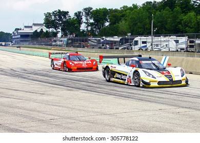 Elkhart Lake, Wisconsin USA - August 9, 2015: Road America road course, IMSA. Action Express Racing, Coyote Corvette DP, Mustang Sampling powered by Chevrolet leads the eventual race winner, pit lane.