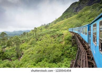 The Ella to Kandy Diesel train locomotive winds through tea plantations near Nuwara Eliya, Sri Lanka.