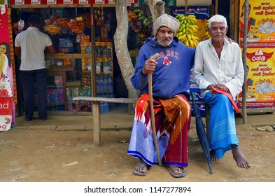 Ella, Sri Lanka - April 10, 2018: Two old Sri Lankan men wearing the traditional sarong and sitting on a bench in front of a grocery store.