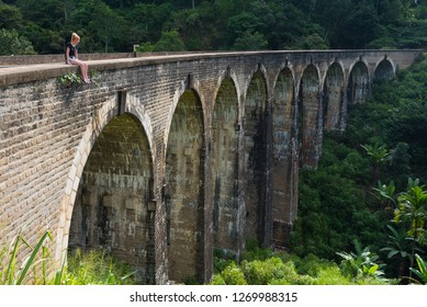 Ella, Sri Lanka, November 23, 2018: A young woman admiring the view from the Nine Arch Bridge in Ella, Sri Lanka