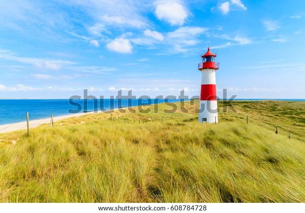 Ellenbogen-Leuchtturm auf Sanddüne gegen blauem Himmel mit weißen Wolken an der Nordküste von Sylt, Deutschland