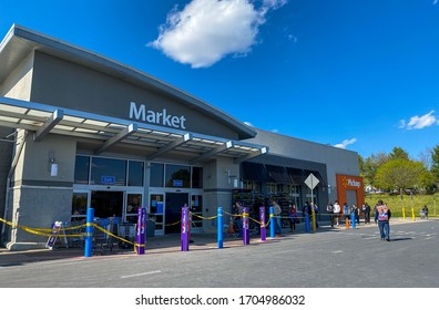Ellicott City, Maryland / USA - April 11, 2020: Shoppers line up outside of Walmart amid the COVID-19 pandemic. Many choose to wear masks to protect themselves and others against the virus.