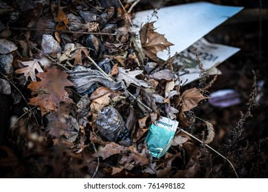 Ellicott City, MD - November 23, 2017: Trash disposed of in a pile of leaves in a Maryland state park.