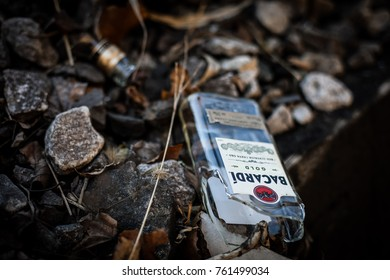 Ellicott City, MD - November 23, 2017: Trash, including a broken Bacardi bottle, is disposed of in a pile of leaves in a Maryland state park.
