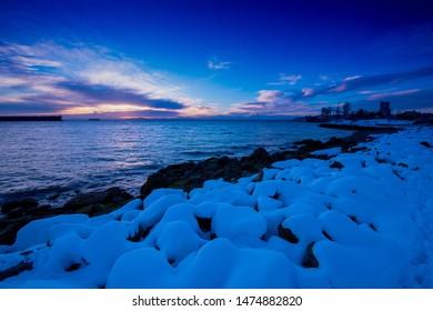 Elliott Bay of Seattle WA. Snow scenery sunset.