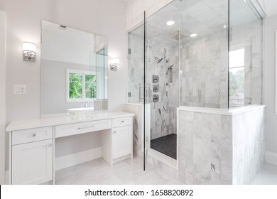 ELMHURST, IL, USA - AUGUST 16, 2019:  A large, luxurious bathroom with a walk in shower lined with marble tiles. A white vanity sits next to the shower with a standalone tub is seen through the mirror