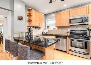 ELMHURST, IL, USA - AUGUST 6, 2020: A small kitchen with maple cabinets, stainless steel Kenmore appliances, bar stools sitting at the granite countertop, and hardwood floors.