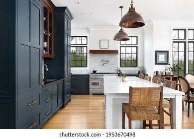ELMHURST, IL, USA - FEBRUARY 24, 2021: A luxurious kitchen with blue cabinets, bronze dome light fixtures hanging above the large white island, and luxury appliances.