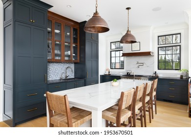 ELMHURST, IL, USA - FEBRUARY 24, 2021: A luxurious kitchen with blue cabinets, bronze dome light fixtures hanging above the large white island, luxury appliances, and a blue tiled backsplash.