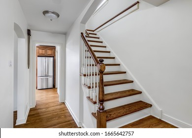 ELMHURST, IL, USA - JANUARY 28, 2020: A white hallway that leads to the kitchen and a set of stairs that go to the second floor with hardwood floors throughout.
