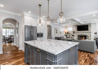 ELMHURST, IL, USA - JANUARY 30, 2020: Looking from a luxurious white kitchen towards a cozy living room and dining room. The living room is fitted with a television mounted above the fireplace.