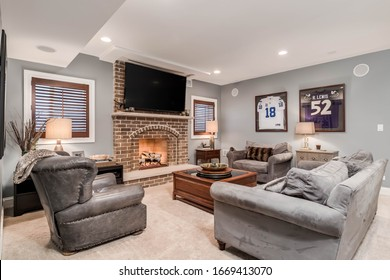 ELMHURST, IL, USA - JANUARY 30, 2020: A man cave, living room with a television mounted above a lit fireplace and football jerseys mounted on the wall.